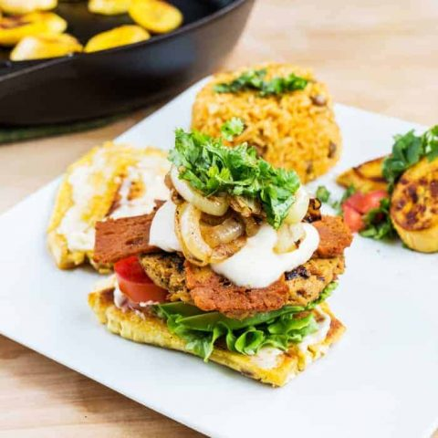 Veggie burger with plantain bun on plate with arroz con gandules
