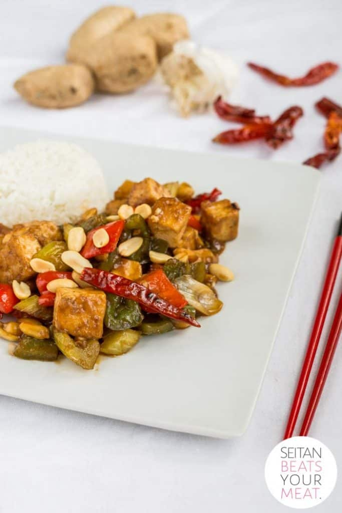 Plate of kung pao tofu and rice with chopsticks, peanuts, and dried chilis