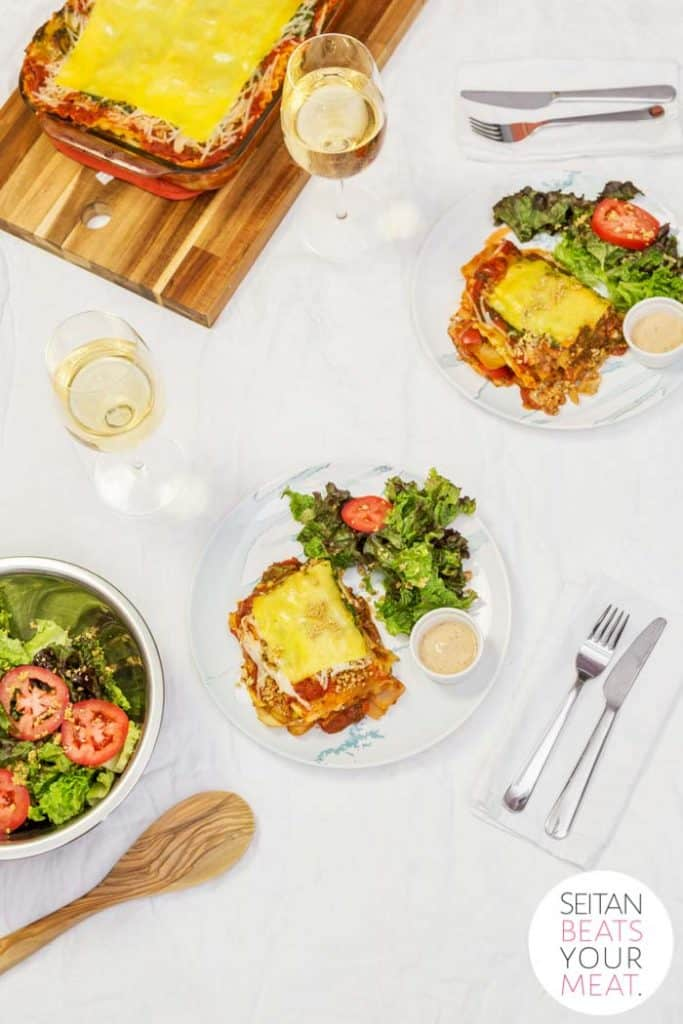 Overhead photo of plated vegan lasagna on white tablecloth