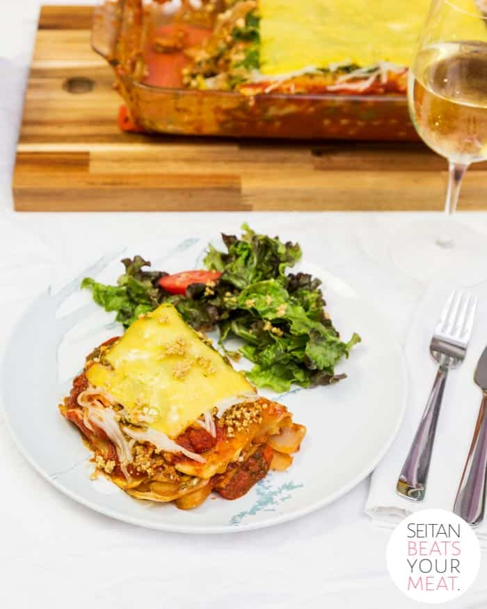 Plate of lasagna and salad with tray of lasagna in background