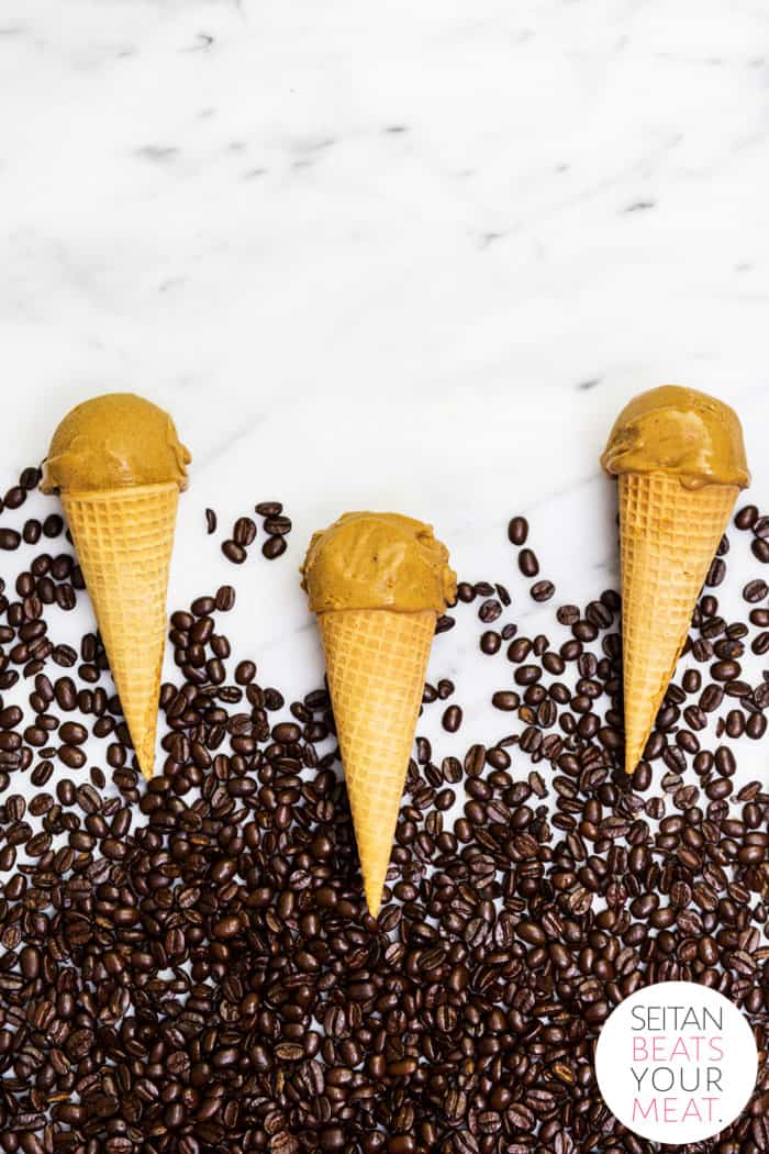 Pumpkin spice ice cream cones with coffee beans on marble