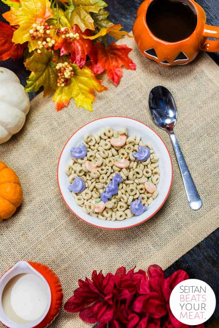 Overhead image of Halloween cereal in a bowl on burlap with Halloween decorations