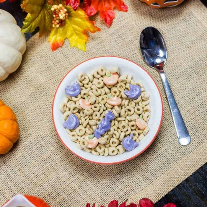 Vegan Halloween Lucky Charms in a bowl on burlap surrounded by pumpkins and fall decor