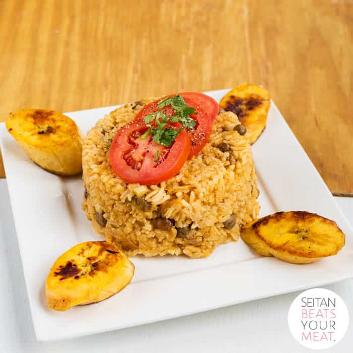 Arroz con gandules with tomatoes and plantains on a white plate on wood background