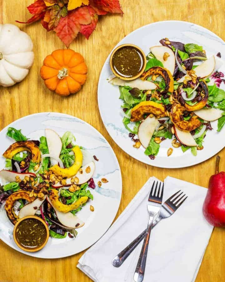 Overhead image of fall salads with pumpkins and pears surrounding the plates