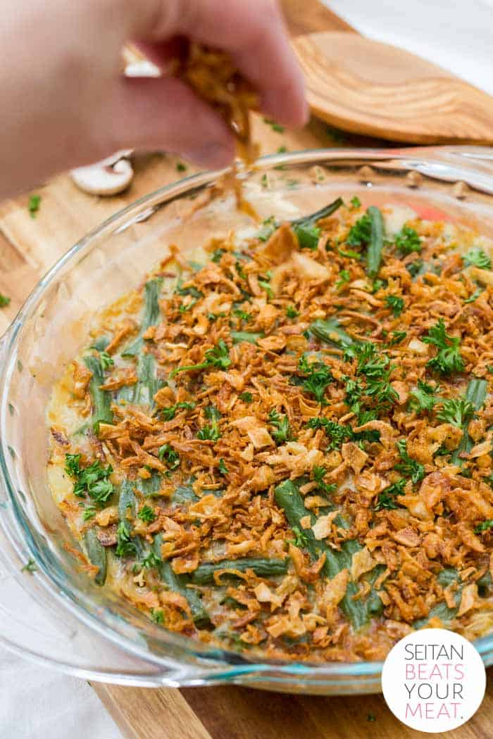 Close up of green bean casserole with hand sprinkling fried onions on top