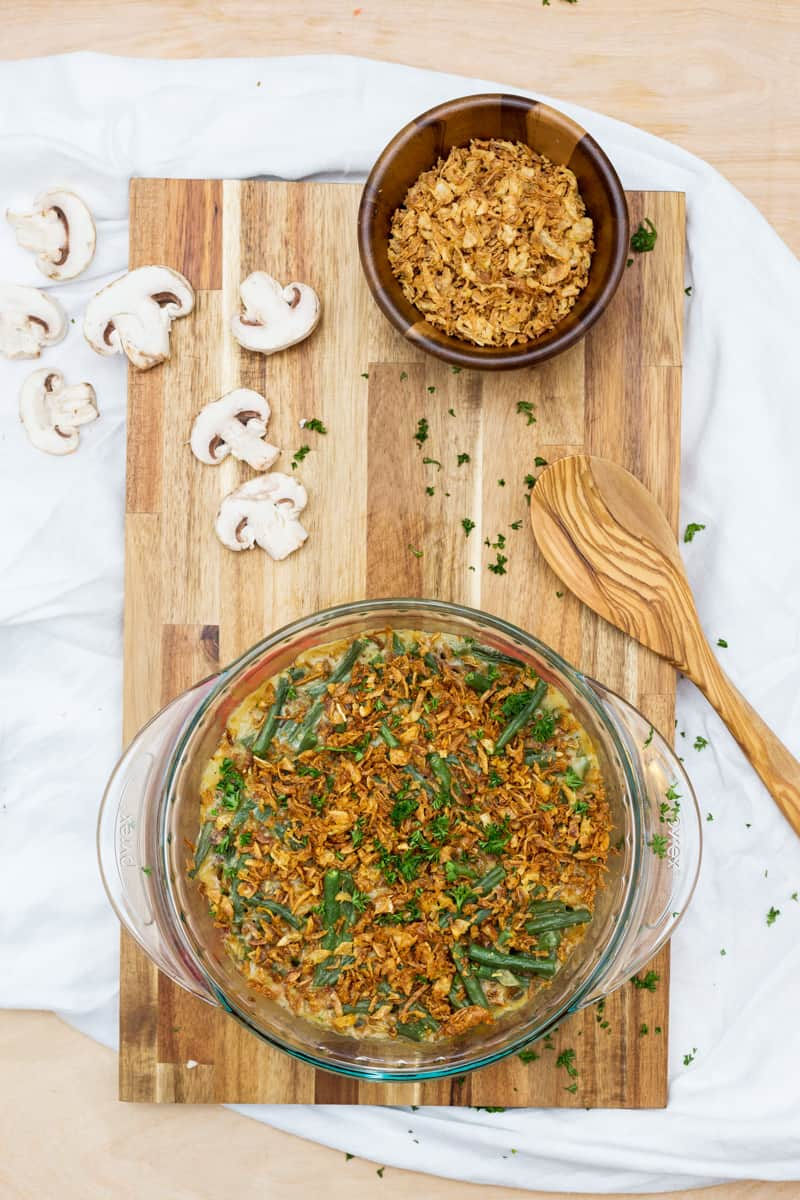 Overhead image of green bean casserole on cutting board surrounded by ingredients