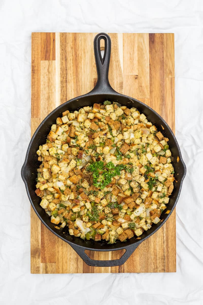 Overhead photo of stuffing in cast iron pan on top of cutting board on white tablecloth