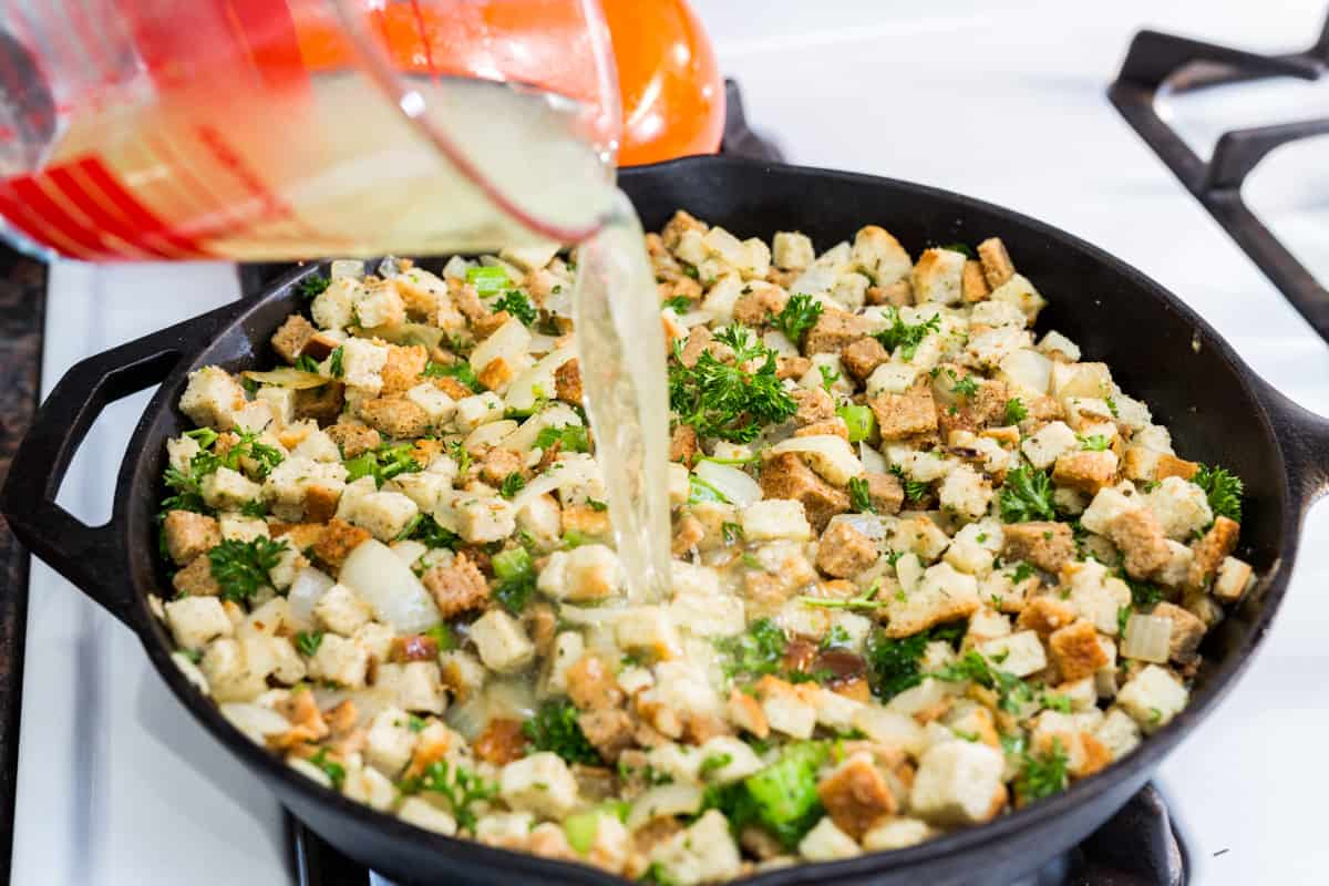 Pouring broth into stuffing in cast iron skillet