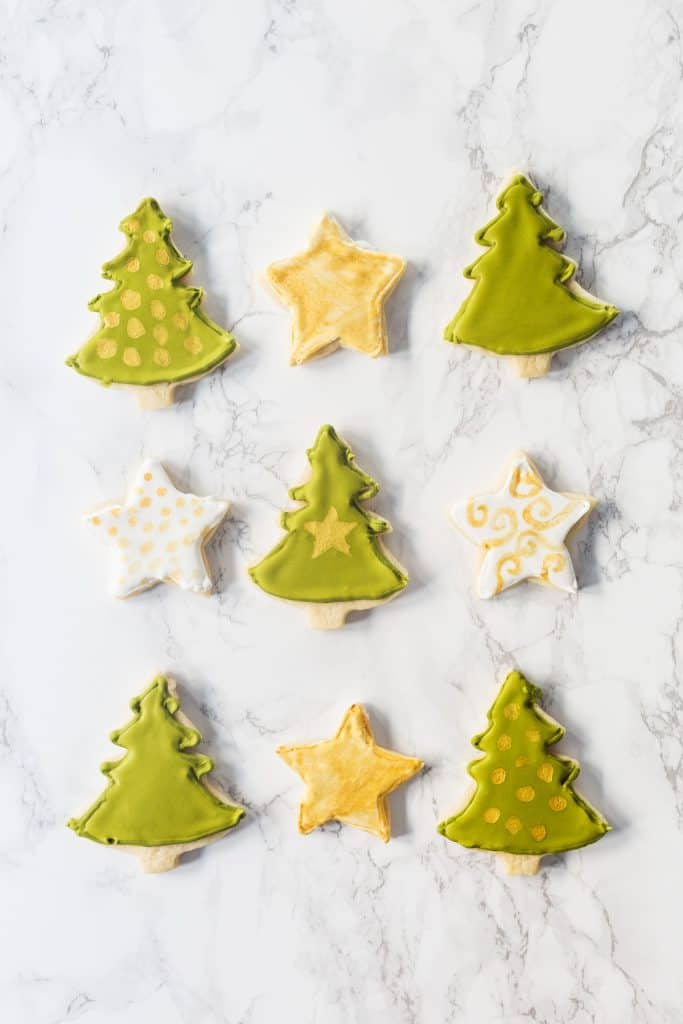 Decorated Christmas tree and star-shaped sugar cookies on marble surface