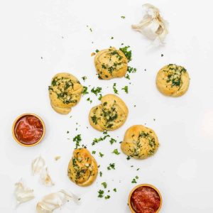 Overhead image of garlic knots with heads of garlic, marinara in cups, and chopped parsley