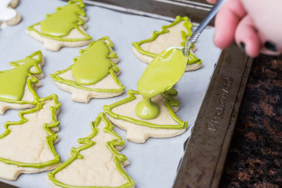 Pouring green royal icing on sugar cookies on cookie tray
