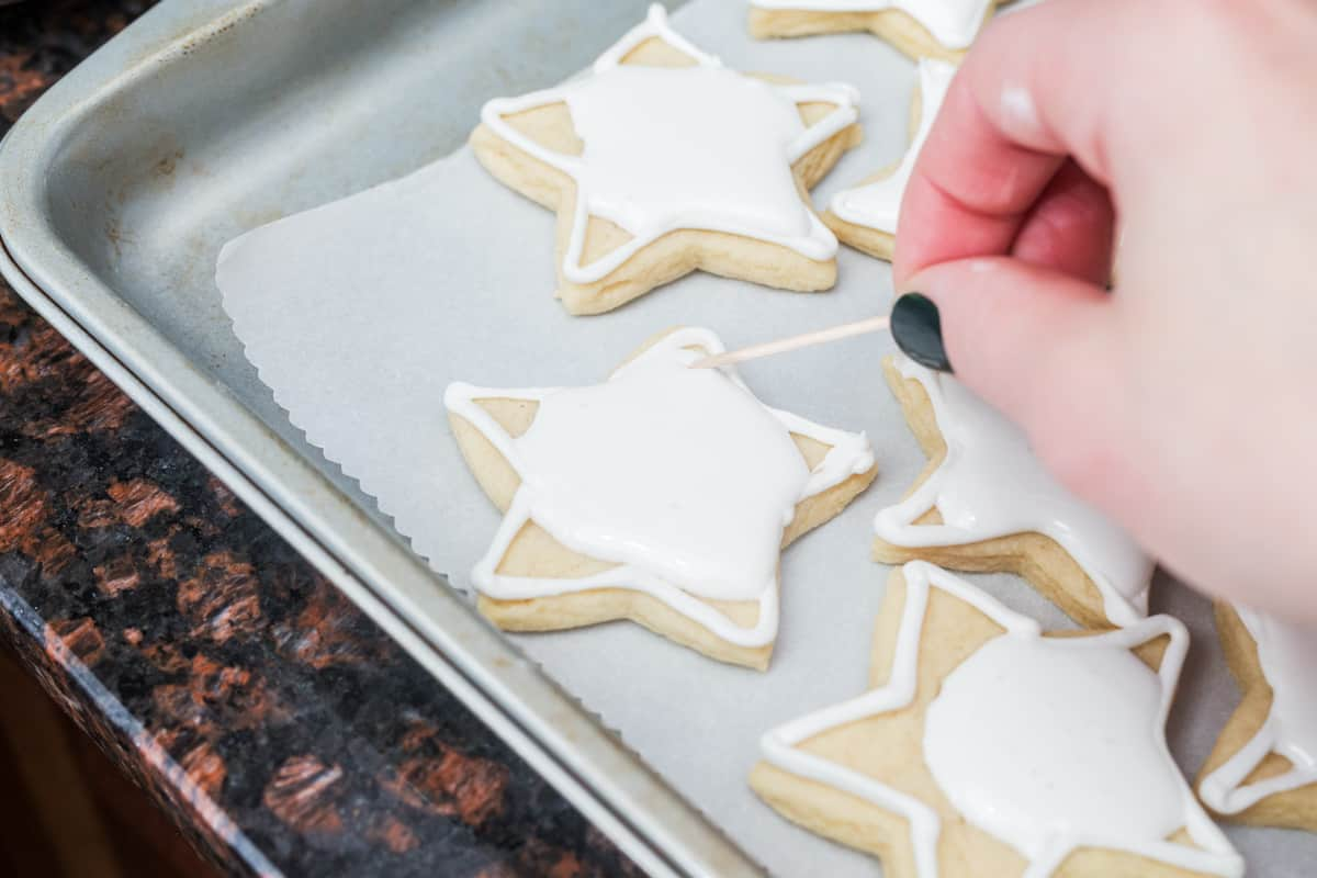 Star-shaped sugar cookies with white royal icing with hand in frame distributing icing with a toothpick