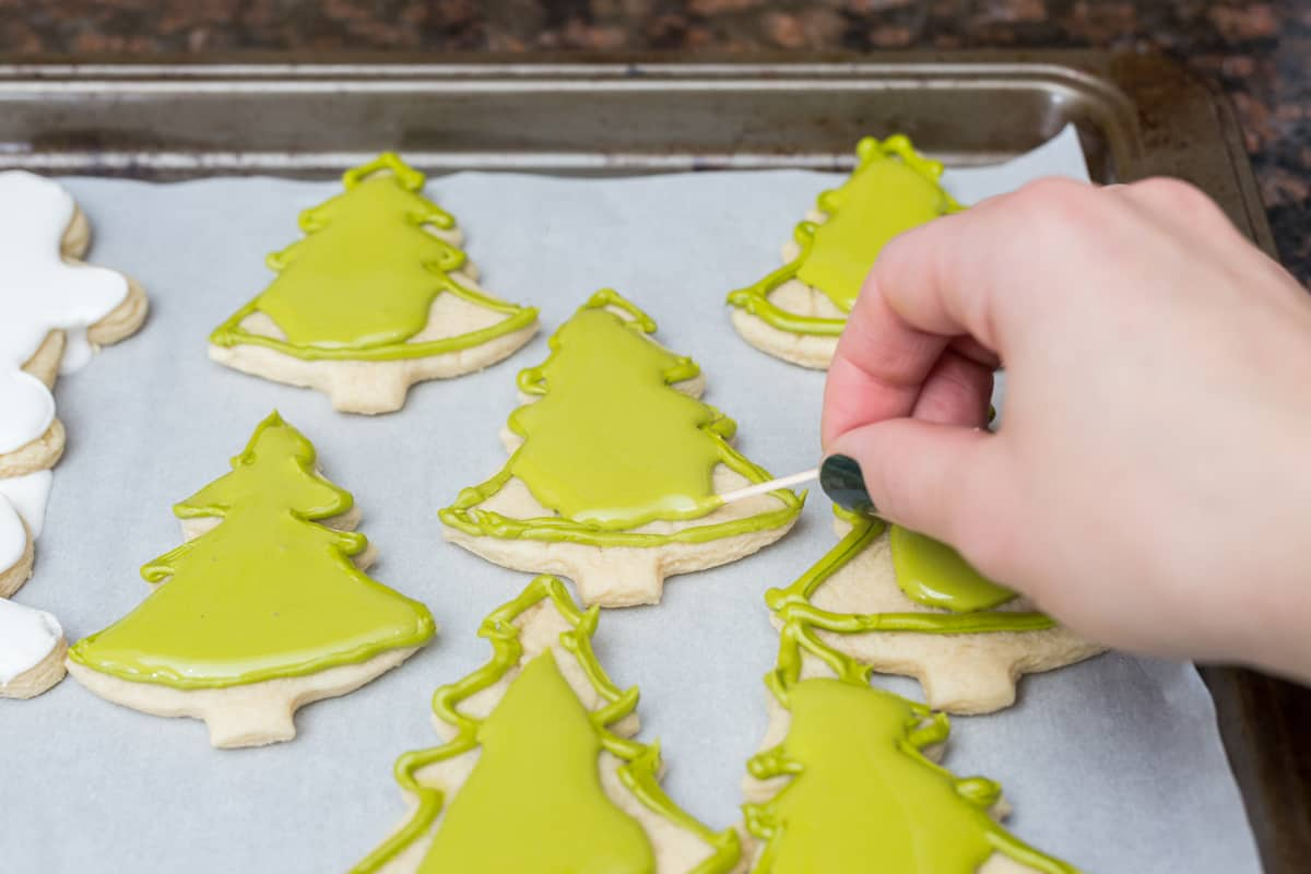 Christmas tree sugar cookies on cookie sheet being decorated with green royal icing