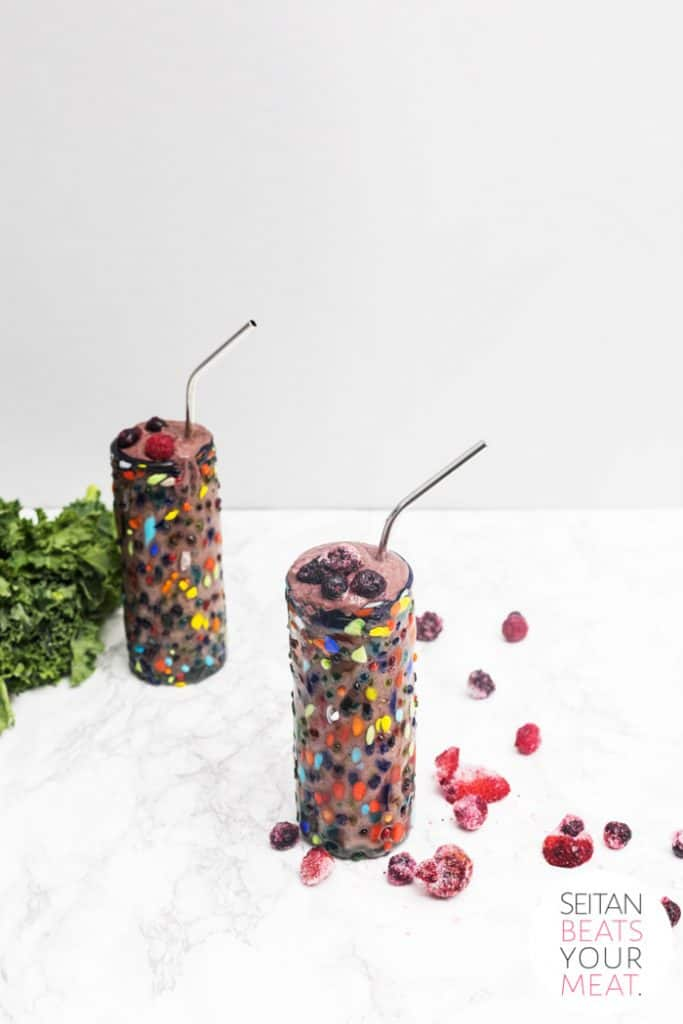 Blueberry avocado smoothie in colorful glass on marble surface