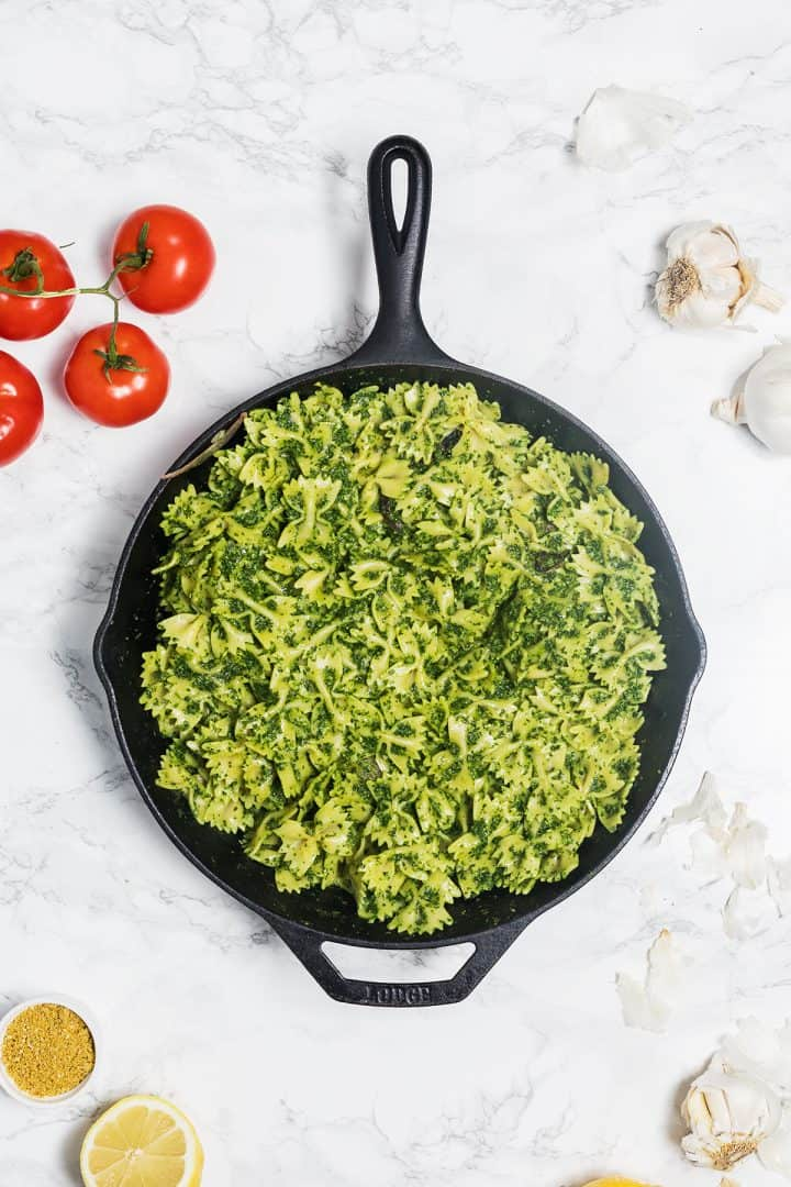 Kale pesto pasta in cast iron pan on marble counter surrounded by tomatoes, garlic, and lemons