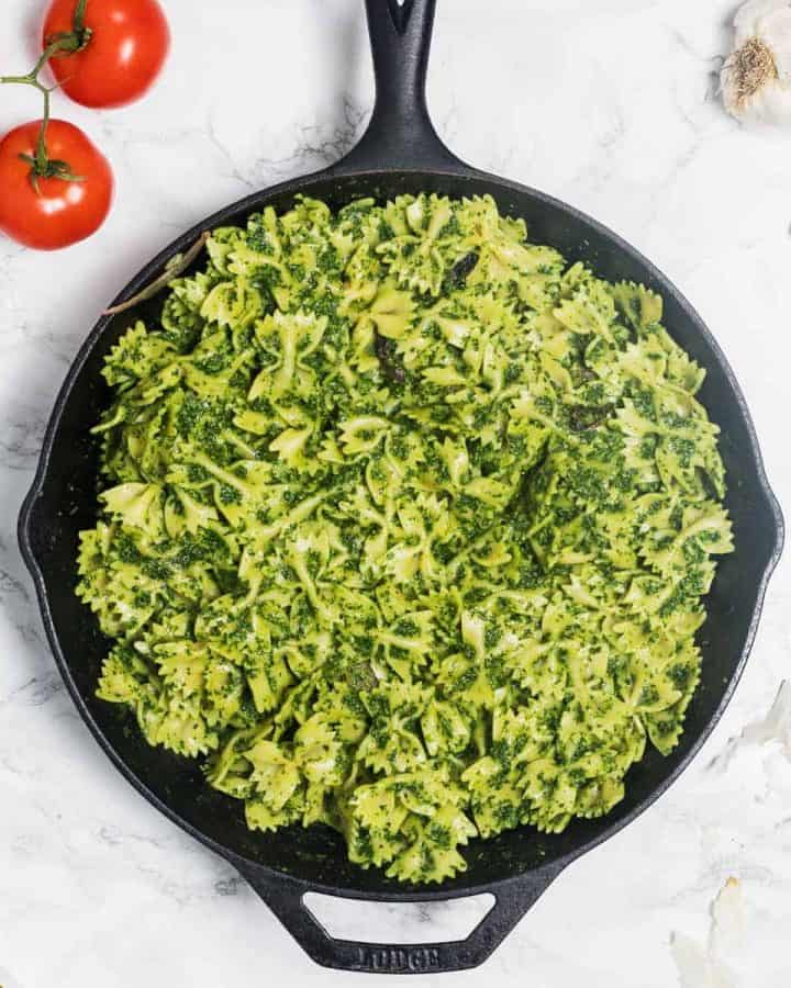 Plate of kale pesto pasta on marble counter surrounded by tomatoes and garlic