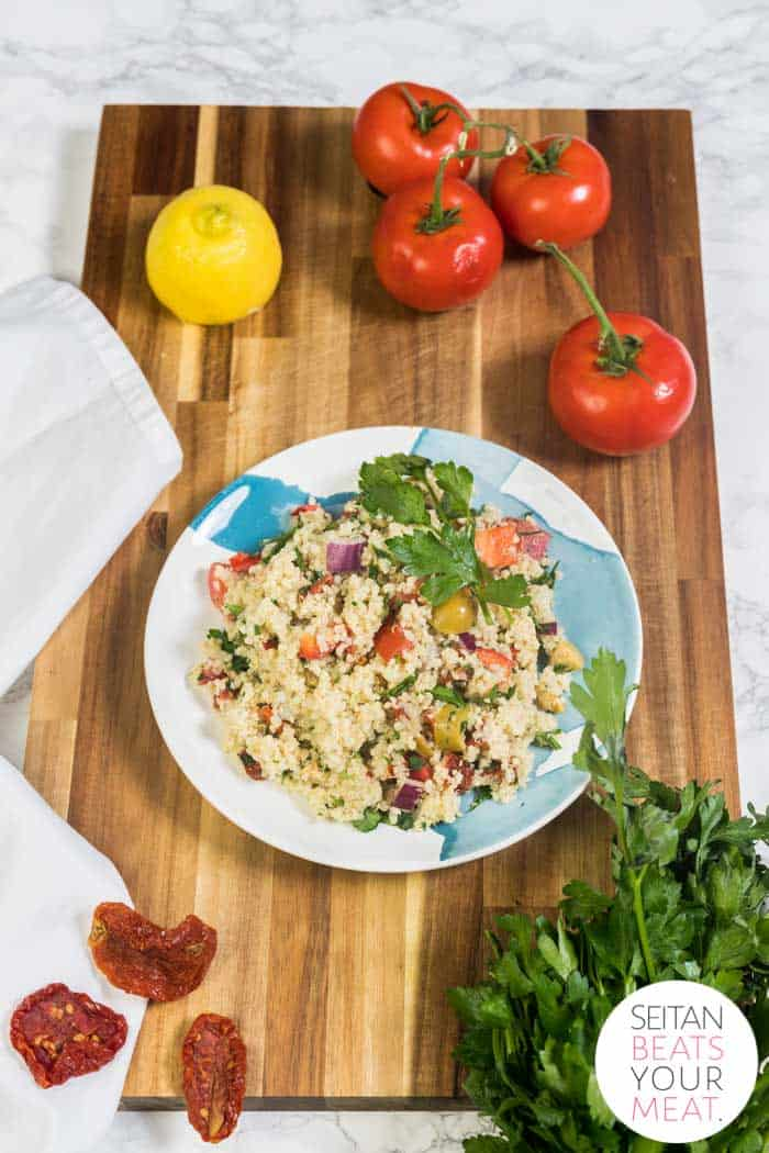 Quinoa salad on plate surrounded by vegetables on cutting board