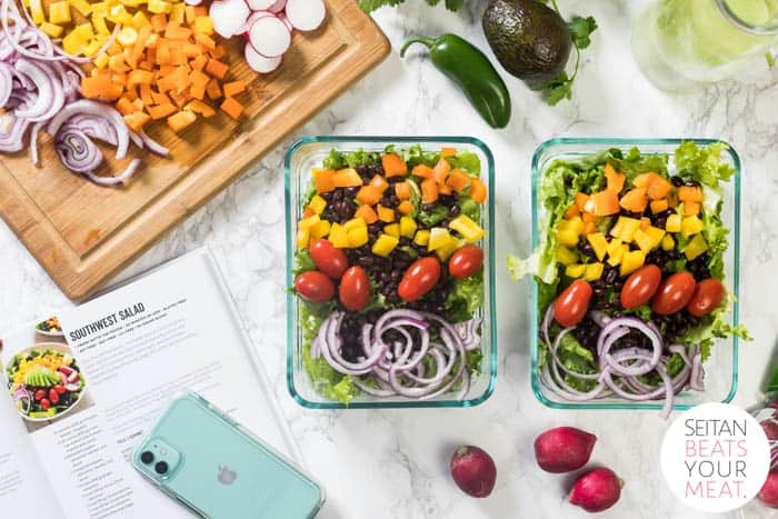 Two glass pyrex containers filled with prepared salad surrounded by fresh vegetables, an iPhone, and a cutting board