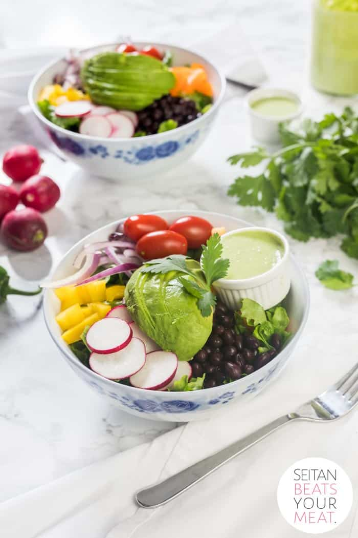 Bowl and container of salad surrounded by vegetables on marble counter