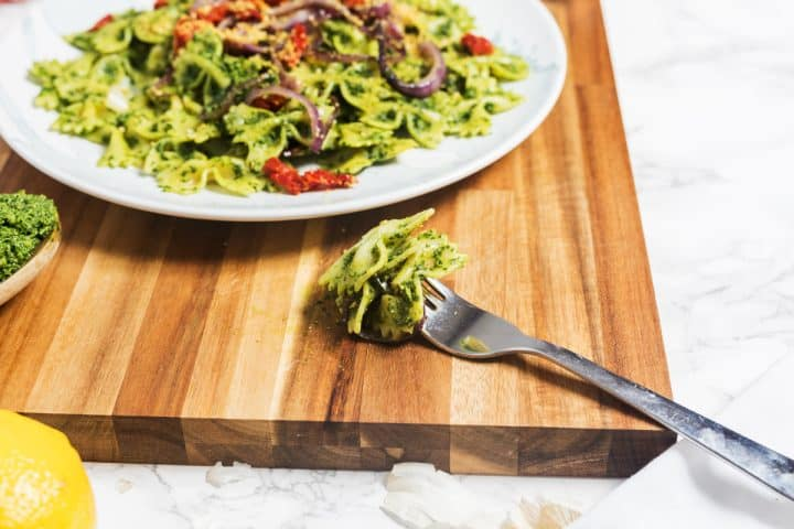 Plate of kale pesto pasta with fork on cutting board on marble counter