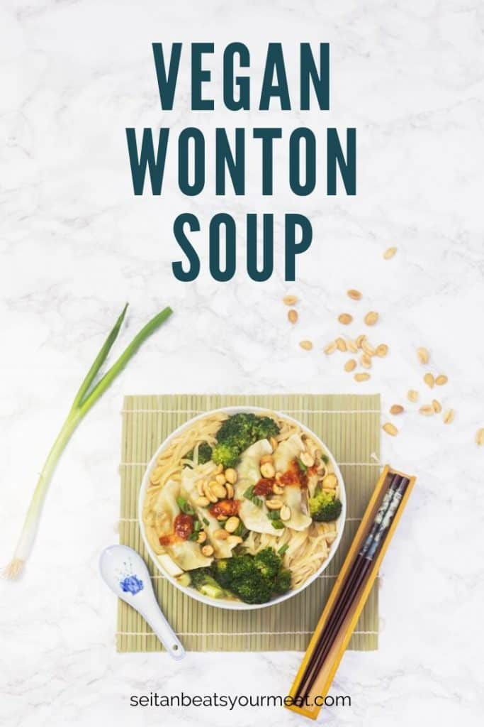 Wonton soup in bowl on bamboo mat with utensils on marble surface