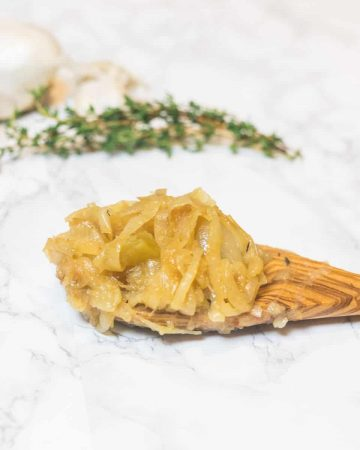 Wooden spoon with caramelized onions on marble counter with thyme and onion in background
