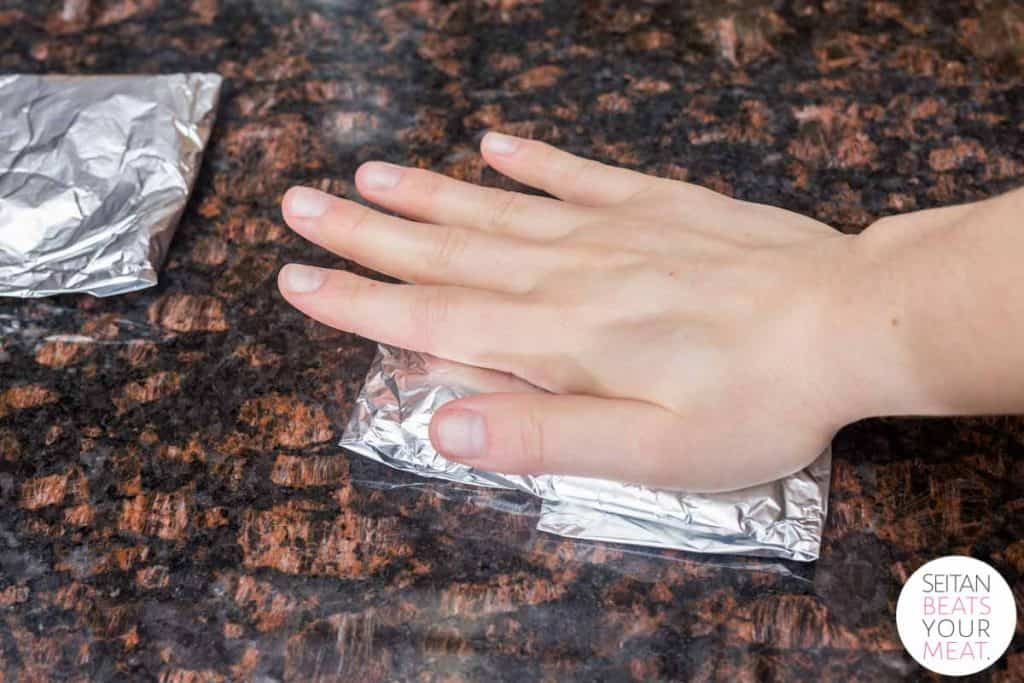 Hand pressing down foil packet of seitan on granite countertop