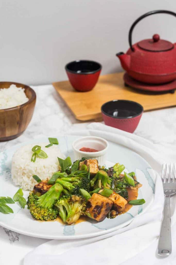 Plate of General Tso's Tofu on white marble counter with red teapot in background