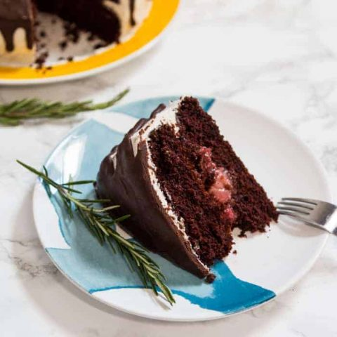 Slice of chocolate cake on plate with sprig of rosemary and rest of cake in background