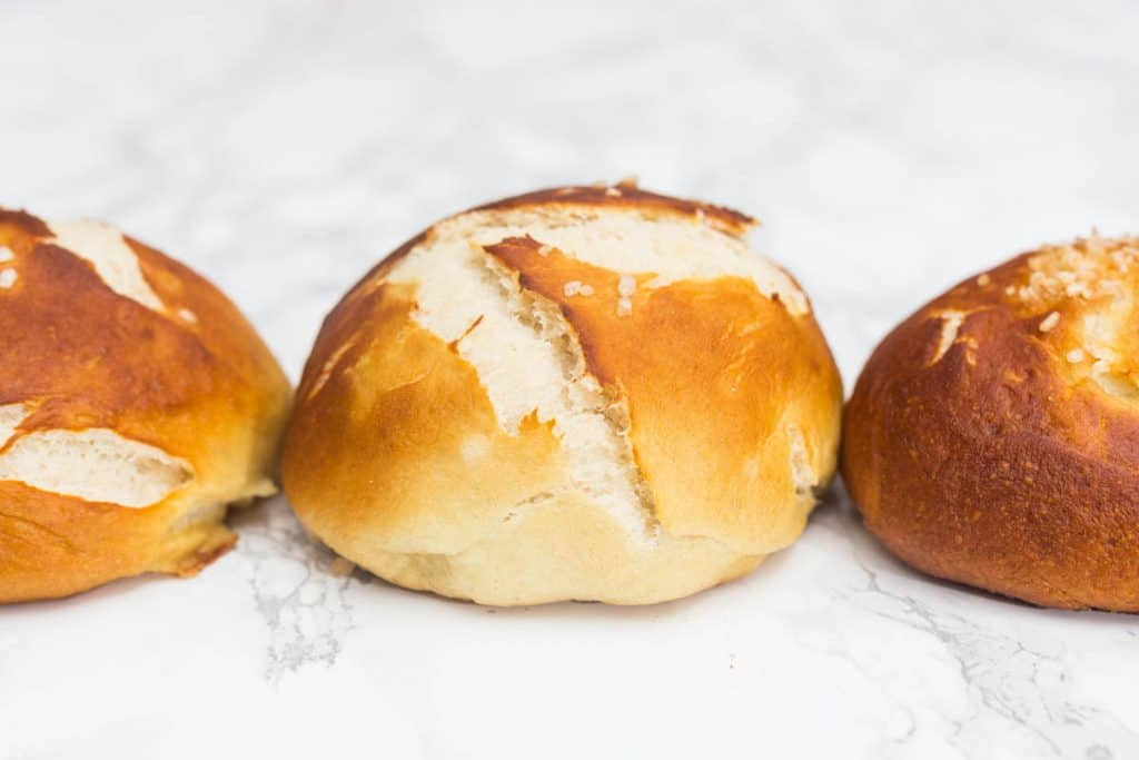Close up photo of 3 pretzel buns on white marble surface