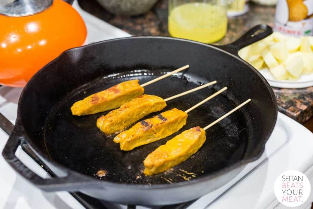 Seitan pieces on skewers cooking in cast iron pan