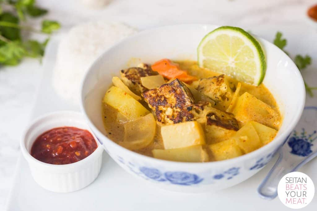 Bowl of yellow curry in bowl on plate with rice surrounded by curry ingredients
