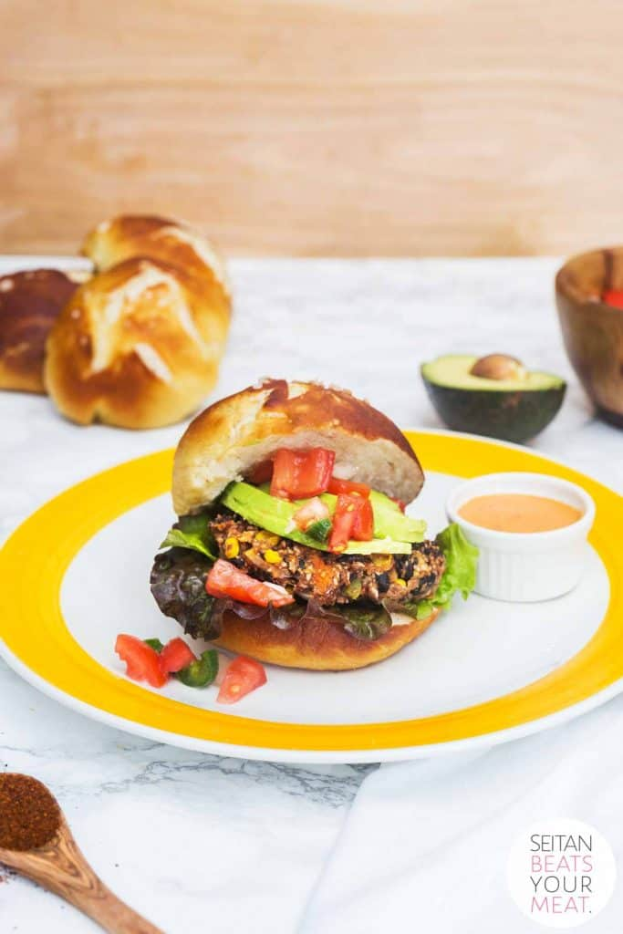 Black bean burger on pretzel bun on yellow plate on white marble counter