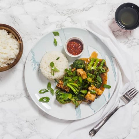 Overhead photo of tofu and broccoli with rice with bowl of rice on side