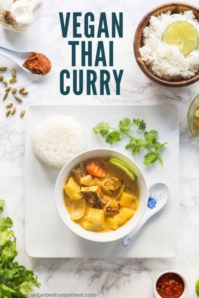 "Bowl of yellow curry in bowl on plate with rice surrounded by curry ingredients and cilantro with text ""Vegan Thai Curry"""