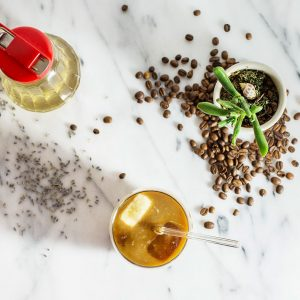 Glass of cold brew coffee on marble counter with coffee beans scattered