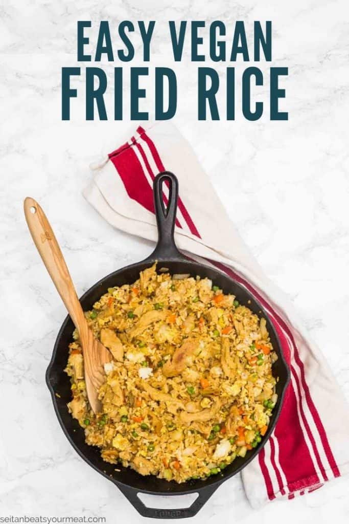 """Cast iron pan with fried rice and wooden spoon on white and red towel with text """"Easy Vegan Fried Rice"""""""