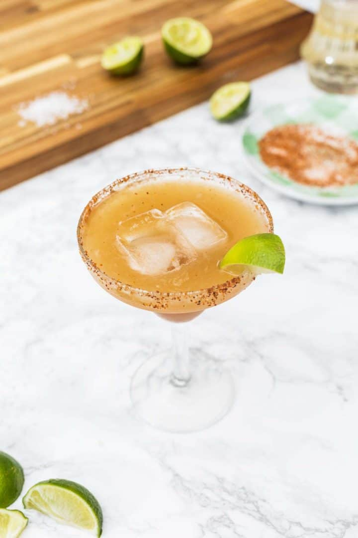 Tamarind margarita with chile rim surrounded by lime slices and cocktail supplies
