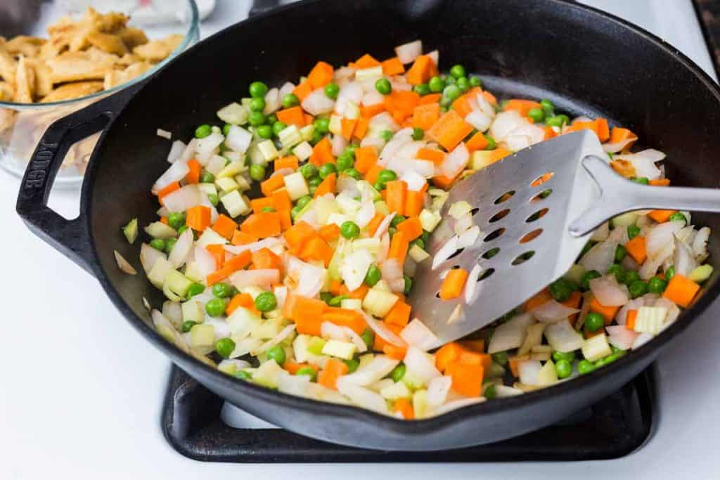 Carrots, peas, onions, and celery in cast iron pan on stove