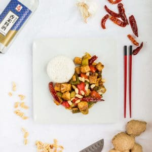 Plate of kung pao tofu surrounded by ingredients and chopsticks