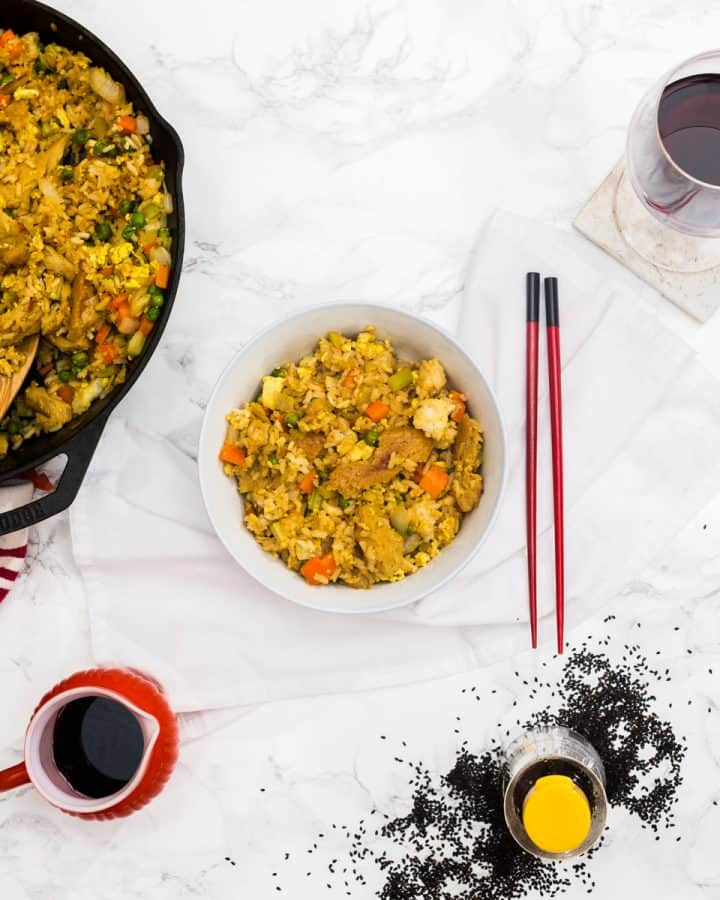 Bowl of fried rice with red chopsticks with glass of wine