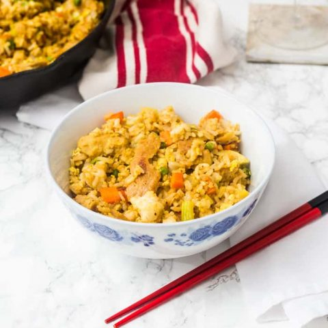 Bowl of fried rice with red chopsticks on white marble surface