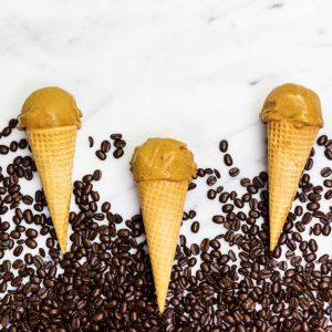 Three ice cream cones with on marble counter with coffee beans scattered