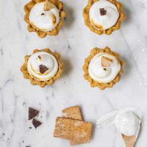 Four small s'mores pies on marble counter