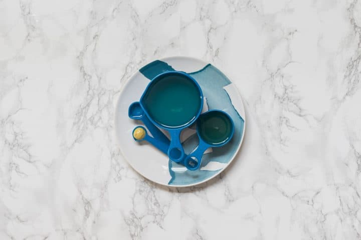 Blue measuring cups filled with ingredients on plate on marble counter