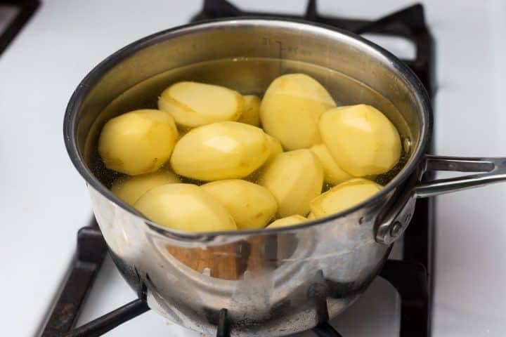 Pot on stove with whole peeled potatoes in water