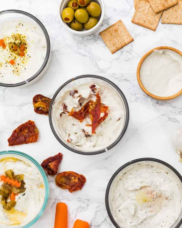 Small bowls of spreadable cheese surrounded by antipasto