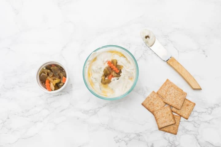 Small bowl of cheese with giardiniera and crackers