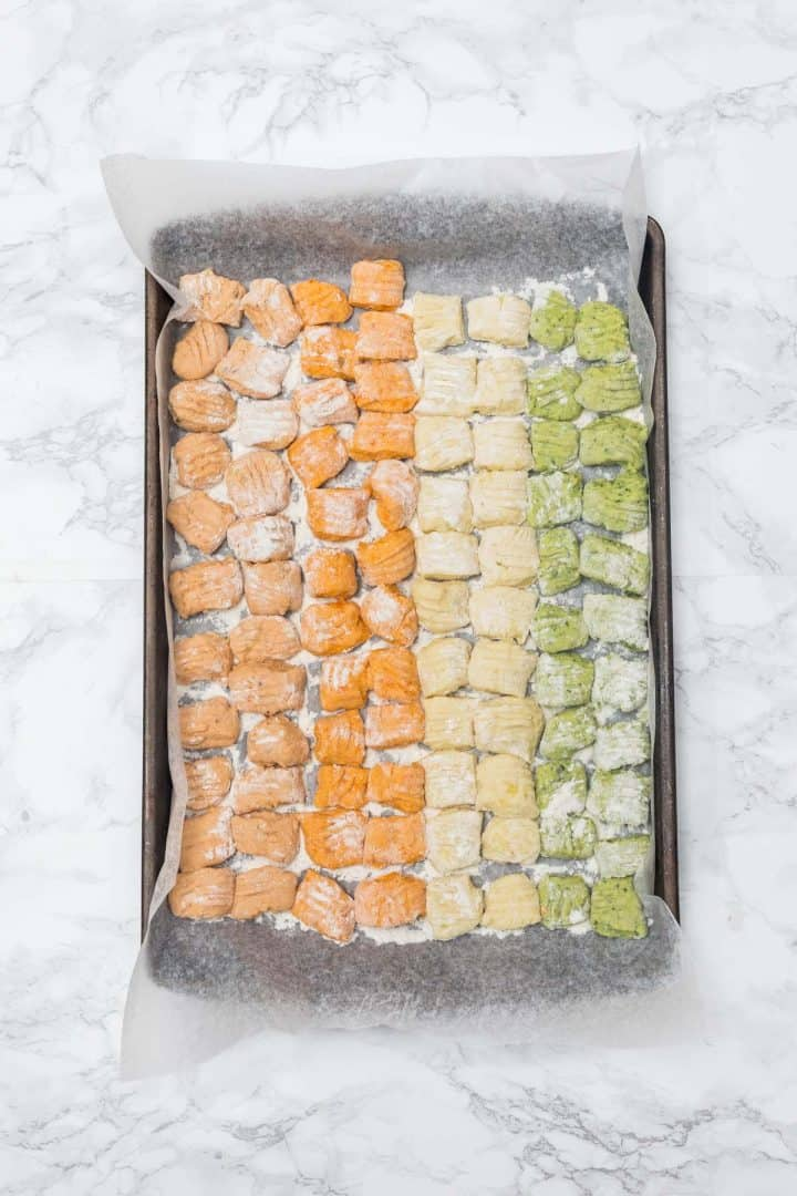 Wax paper-lined tray of uncooked gnocchi sorted by color - red, orange, plain, and green